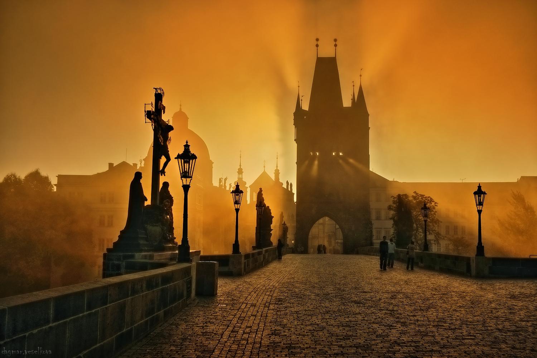 """Dagmar Veselková: """"Slunce a mlha dovedou na Karlově mostě vytvořit někdy až neskutečné obrazy. Tohle ráno jsem se zatajeným dechem sledovala, jak se z mostecké věže stal Golem, oživený slunečním šémem – jen se dát do pohybu…"""""""