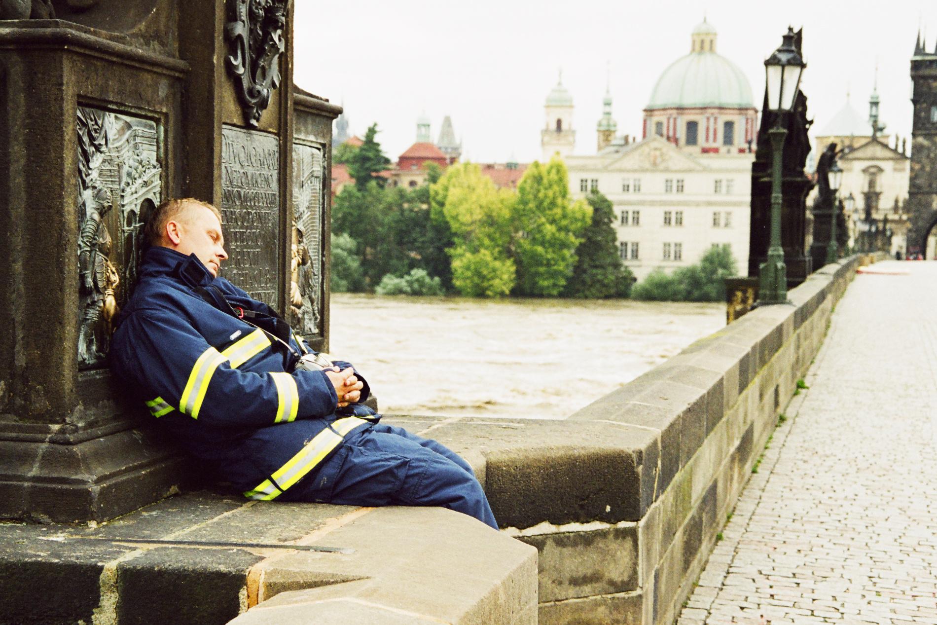 Na chvilku se udělalo docela hezky a Kráťa (Václav Kratochvíl) po 34 hodinách odsloužených na Karlově mostě usnul pod sochou, na niž si lidé sahají pro štěstí. Velel akci, která zachránila most, po němž šly naše dějiny i stamiliony turistů. Vltava předtím unášela chaty, lodě, patnáct metrů vysoké silo, ale i pětitunový zásobník na propan-butan. Ještě s jedním mužem z Povodí Vltavy Kráťu napadlo povolat bagr s dlouhým ramenem. Co šlo, rozbíjeli na menší kusy ještě před nárazem do pilířů, nebo to alespoň nasměrovali mezi mostní oblouky. - (Foto: Jaromír Chalabala)