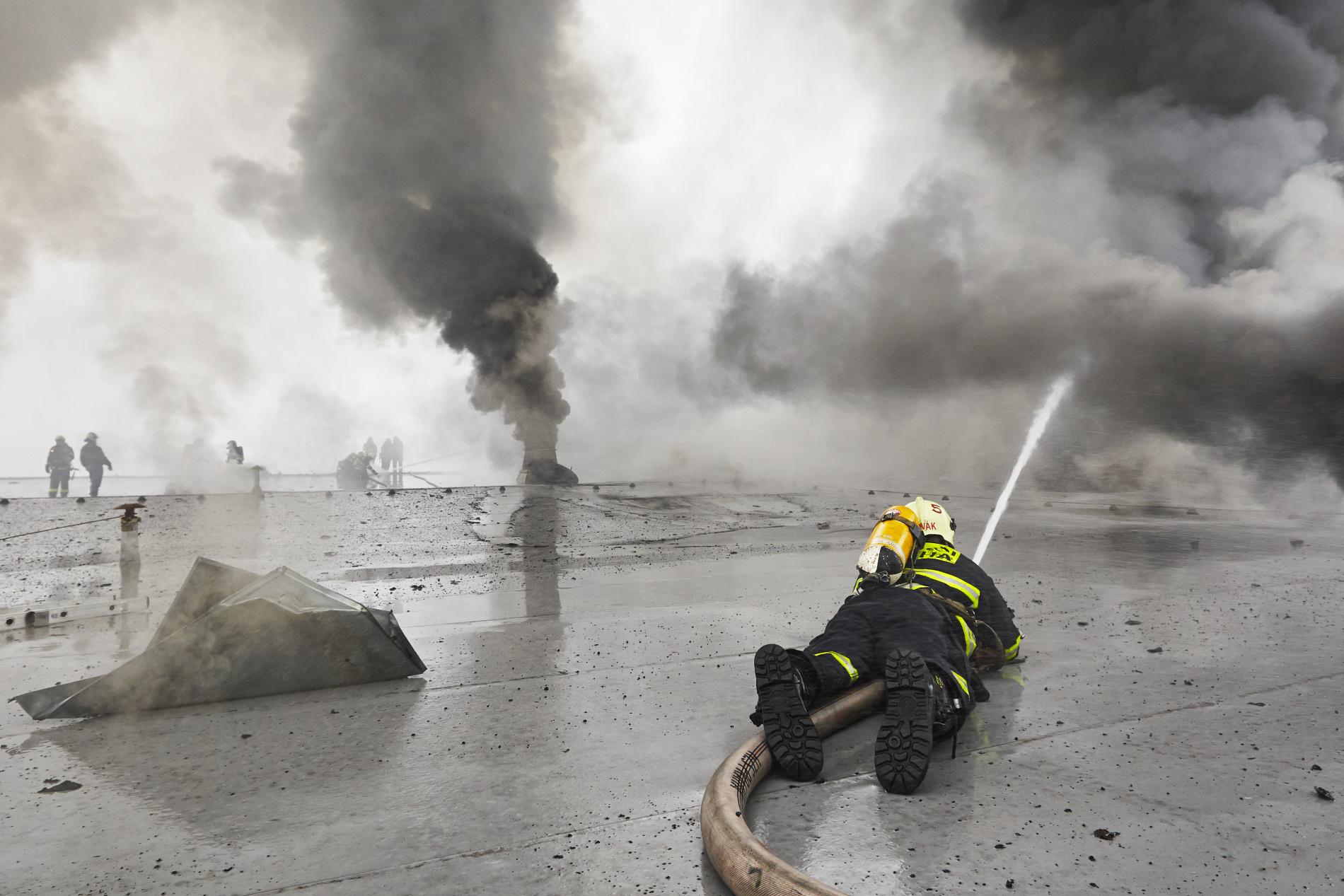 Po řadě ústupů se však blíží chvíle, kdy se situace otočí. Všichni hasiči na střeše hořícího velkoskladu v pražské Libuši tomu věří. - (Foto: Jaromír Chalabala)