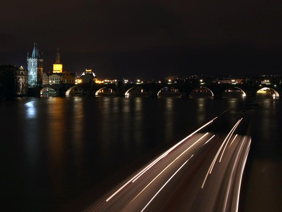 Vesměs všechno, co večer svítí a projíždí může při dlouhé expozici vytvořit nádherný efekt – tady projížděla zrovna večerní plavba po Vltavě