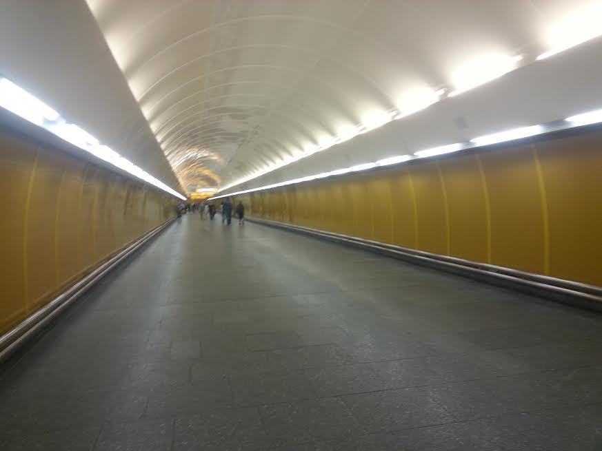 Dlouhá chodba mezi nástupištěm a eskalátory