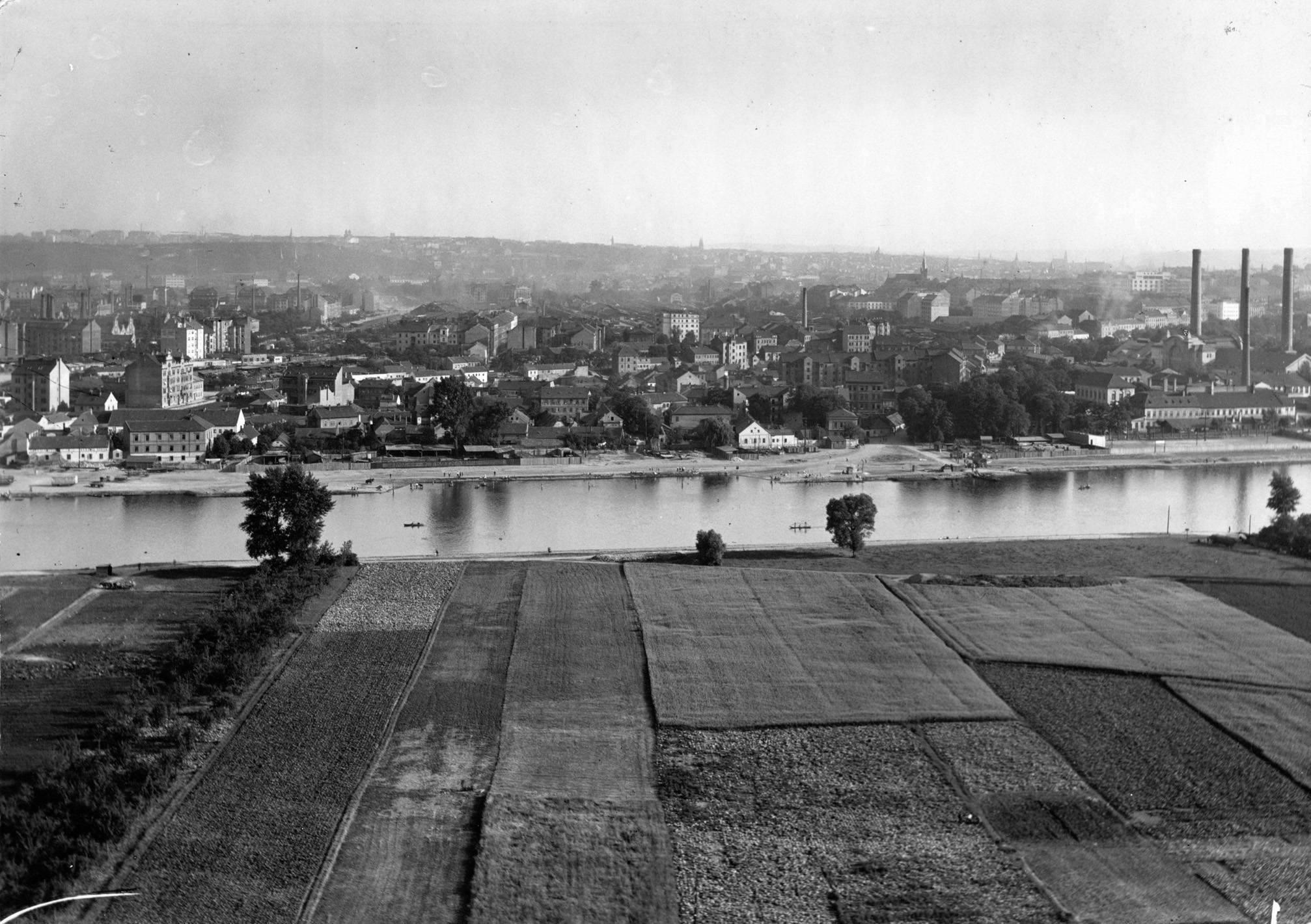 Tento snímek z roku 1928 navazuje na předchozí a ukazuje staré Holešovice, půvabnou vesnici na břehu Vltavy, prakticky zcela zničenou při výstavbě holešovického nádraží v osmdesátých letech 20.století. Zcela vpravo jdou vidět charakteristické komíny holešovické elektrány, která se dodnes částečně zachovala v sousedství Stromovky a areálu holešovického výstaviště. - popisky sepsal architekt Petr Kučera