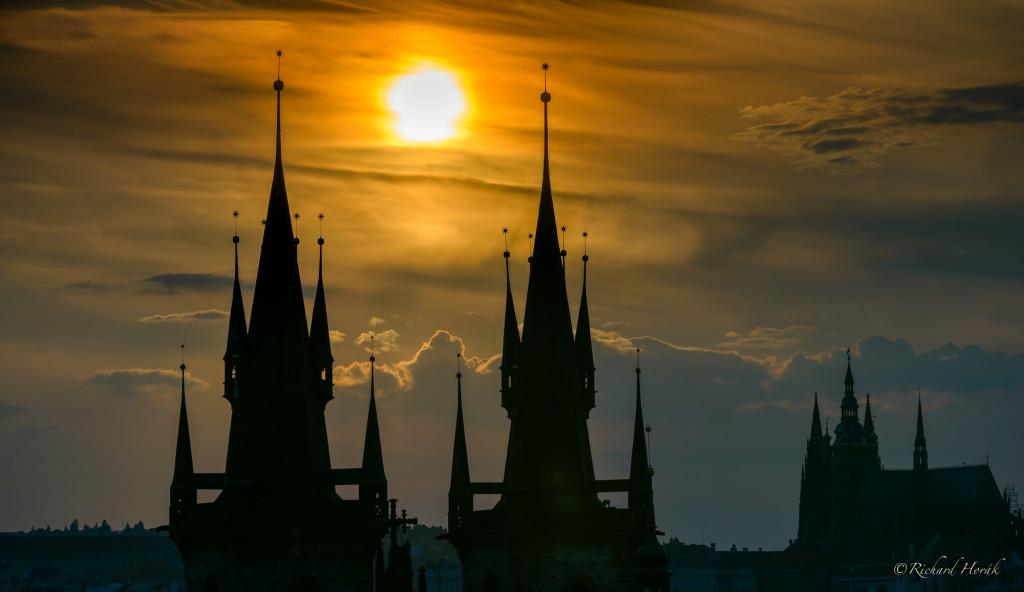 """""""Fotografie věží Týnského chrámu z Prašné brány při západu slunce, pokoušel jsem se mít slunce mezi nimi. Ještě jsem je doplnil Pražským hradem."""" - Foto: Richard Horák"""