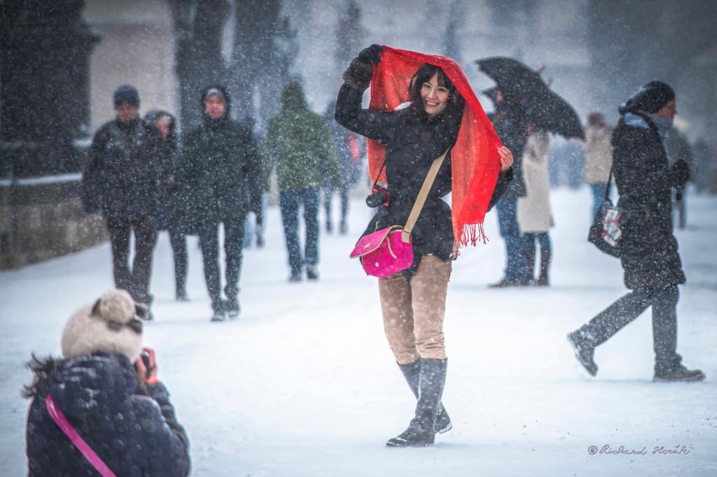 """""""I když to není přímo fotografie Prahy ale krásné turistky na Karlově mostě, tu jsem vyfotil při velmi hustém sněžení a ona se krásně dívala a usmívala na mne místo na svojí kamarádku, která ji fotila... Tuhle fotografii mám velice rád, právě pro tu krásnou slečnu s optimistickým nádherným úsměvem a měl jsem s ní radost navíc třikrát! Poprvé, když jsem ji doma viděl v počítači, podruhé v loni, kdy jsem s ní vyhrál cenu Foma Bohemia 3.6.2013, na výstavě fotografií 17. ročníku Praha fotografická. A překvapivě ještě znovu letos 10.6.2014, jsem s ní získal"""" - Foto: Richard Horák"""