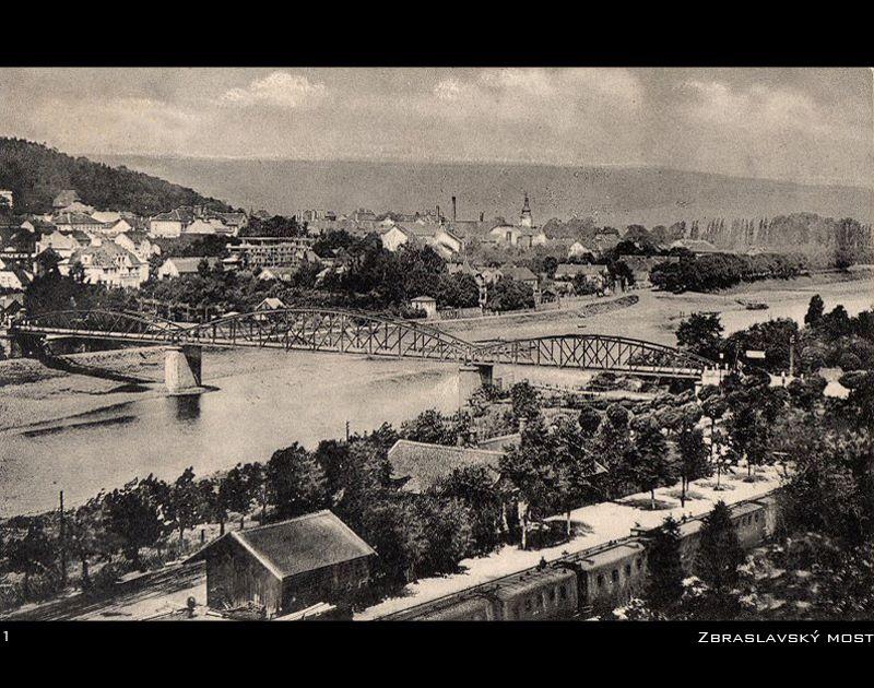 Předchůce mostu Závodu míru na Zbraslavi. Původně stál v těchto místech železný most nazývaný Zbraslavský most o třech polích, který byl vybudován nákladem 136 tis. zlatých v roce 1896. V roce 1964 byl nahrazen novým železobetonovým mostem (most Závodu míru), vybudovaným o něco níže po proudu řeky.