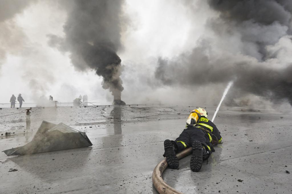 Hasiči na střeše hořícího velkoskladu v pražské Libuši - Foto: Jaromír Chalabala