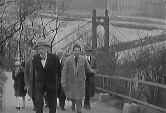 Muži kráčející ve třicátých letech 20. století na Letenskou pláň, aby shlédli fotbalové utkání. Za nimi Štefánikův most, dříve most císaře Františka Josefa I.