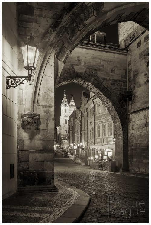 MOSTECKÁ VĚŽ Brána mezi dvěma Mosteckými věžemi. Čekání na prázdnou ulici bylo nekonečné a také zbytečné. Pomyslně jsem si fotku rozdělil na několik sektorů, z nichž měl být vždy alespoň jeden liduprázdný. Pak už to jen doma složit dohromady. Takováto místa je lepší fotit v lednu. - Foto: Ivan Bárta