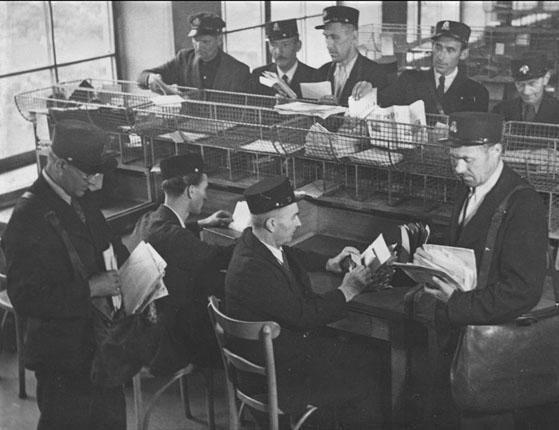Listonoši se připravují na roznášku (1946) - Foto: archiv České pošty
